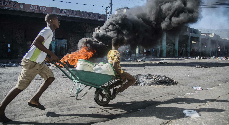 Un hombre permanece fuera de un establecimiento que fue quemado junto a un vehículo durante las protestas de Puerto Príncipe. 9/7/2018
