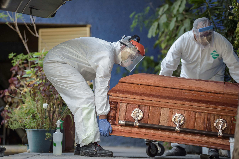 Empleados de una funeraria con indumentaria protectora como protección por el coronavirus mueven un ataúd en un crematorio del distrito de Xochimilco, el 4 de mayo de 2020 en Ciudad de México.
