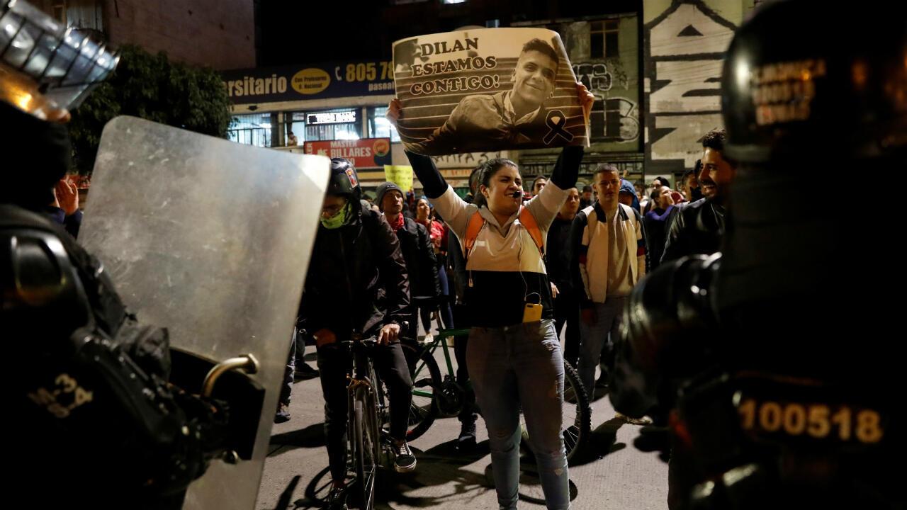 Una manifestante sostiene un cartel con la imagen de Dilan Cruz en frente de un grupo de agentes del ESMAD el pasado 26 de noviembre en Bogotá, Colombia.