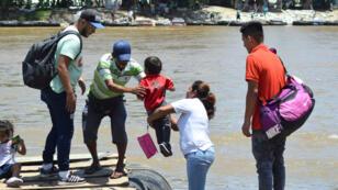 Migrantes guatemaltecos embarcan con su hijo en una balsa para cruzar hacia Ciudad Hidalgo, México. Guatemala, el 17 de julio de 2019.
