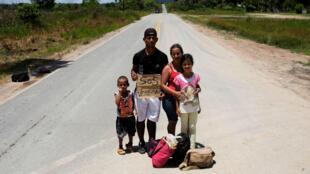 Una familia venezolana del estado de Aragua posa para una foto mientras intentan hacer autostop hacia la ciudad de Boa Vista, después de obtener el estatus de refugiado o residencia temporal, a través de la Policía Federal y el Alto Comisionado de las Naciones Unidas para los Refugiados (ACNUR), en el Control fronterizo de Pacaraima, estado de Roraima, Brasil, el 10 de agosto de 2018.