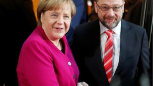 Angela Merkel y Martin Schulz se dan la mano previo al inicio de las conversaciones para formar un gobierno de coalición