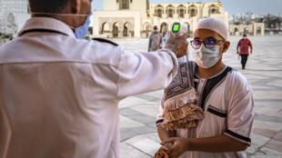عامل يقيس درجة حرارة جسم المصلين المسلمين الوافدين للصلاة في مسجد الحسن الثاني في الدار البيضاء يوم 16 حزيران/يونيو 2020.