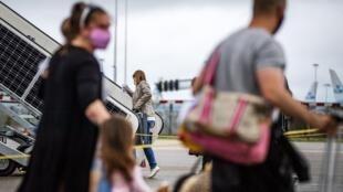 ركاب في طريقهم لاستقلال طائرة في مطار امستردام سيبهول الهولندي في 1 تموز/يوليو 2020.