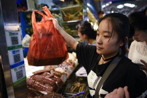 Une femme sur un marché de fruits de mer à Pékin.