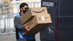 Un conductor de reparto de Amazon.com Inc. lleva cajas a una camioneta fuera de una planta de distribución, el 2 de febrero de 2021, en Hawthorne, California.