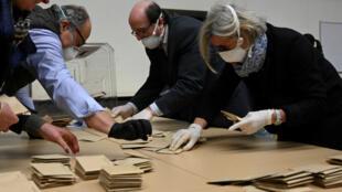 Des agents électoraux portant des masques de protection et des gants procèdent au dépouillement des bulletins de vote après le premier tour des élections municipales dans un bureau de vote à Strasbourg, le 15 mars 2020.