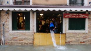 Un homme évacue de l'eau de sa boutique, le 15 novembre 2019, à Venise.