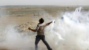 فلسطيني يرمي قنبلة مسيلة للدموع خلال مواجهات قرب السياج الأمني مع إسرائيل بقطاع غزة الجمعة 18 أيار/مايو 2018