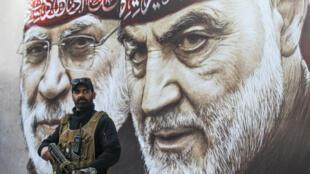 An Iraqi fighter of the largely pro-Iran Hashed al-Shaabi paramilitary force stands guard beneath portraits of slain Iranian Revolutionary Guards commander Qasem Soleimani (R) and Abu Mahdi al-Muhandis