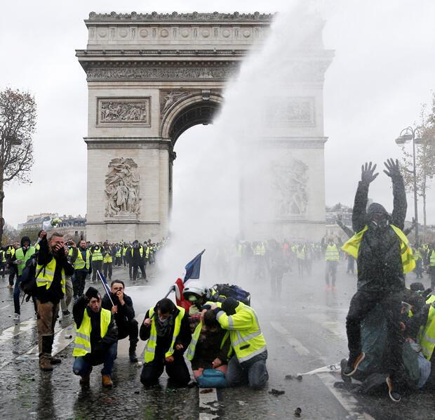 Algunos 'chalecos amarillos', un símbolo de la protesta de los conductores franceses contra los impuestos a los combustibles, se paran frente a un cañón de agua de la policía cerca del Arco de Triunfo en París, Francia, el 1 de diciembre de 2018.