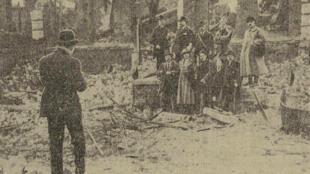 Une photographie sur le premier train de pèlerinage montrant des touristes dans des ruines d'une ville dévastée, extrait d'un article de l'Excelsior du 12 mai 1919.