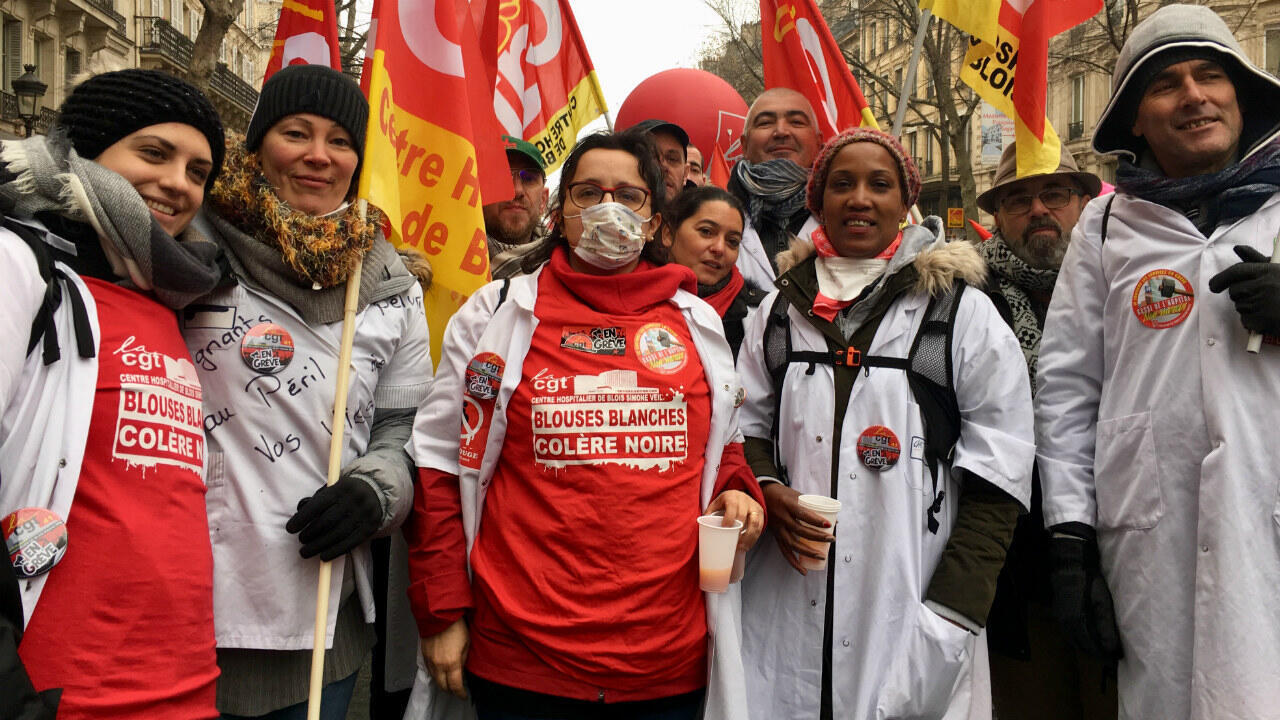 Hospital workers including Thierry Fromont (R), a representative in the CGT union in Blois, France, march against President Emmanuel Macron's proposed pension reform in Paris on December 5, 2019.