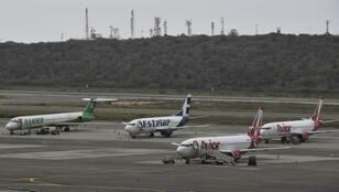 Commercial planes sit on the tarmac at Simon Bolivar International Airport in Maiquetia, in the state of Vargas, northern Venezuela, on March 8, 2019 during the worst power outage in the country's history