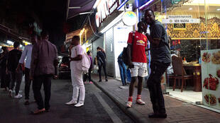 """This file photo taken on March 2, 2018 shows people gathering on a street in the """"Little Africa"""" district in Guangzhou, the capital of southern China's Guangdong province."""