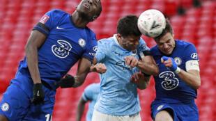 Le milieu de terrain espagnol de Manchester City, Rodrigo, aux prises avec les défenseurs de Chelsea, le Français Kurt Zouma (g) et l'Espagnol Cesar Azpilicueta, lors de leur demi-finale de la Coupe d'Angleterre, le 17 avril 2021 au stade de Wembley à Londres