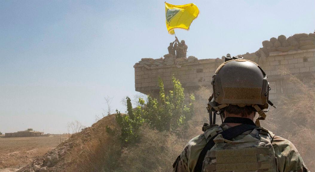 Un soldado de EE. UU. Supervisa a miembros de las Fuerzas Democráticas Sirias, mientras derriban una fortificación YPG y levantan una bandera del Consejo Militar Tal Abyad sobre el puesto avanzado como parte del acuerdo de zona de mecanismo de seguridad, en Siria el 21