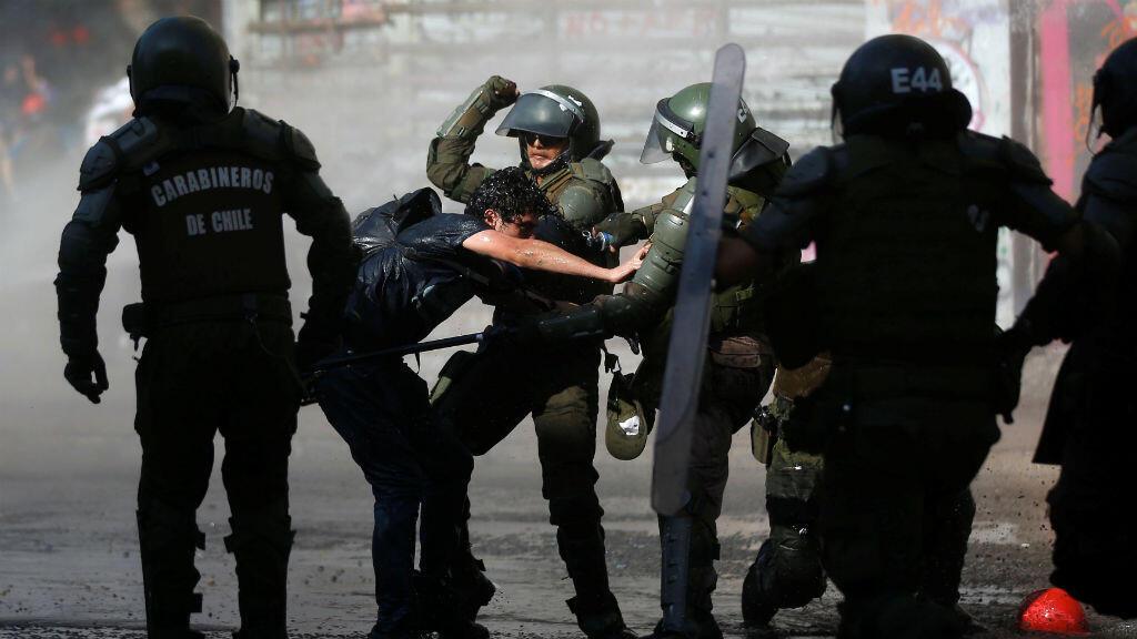 Las fuerzas de seguridad chocan con un manifestante durante una protesta contra el gobierno de Chile en Santiago, Chile, el 3 de enero de 2020.