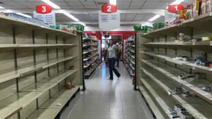 Una mujer pasa frente a estanterías vacías en un supermercado en Caracas, Venezuela, el 6 de enero de 2018.