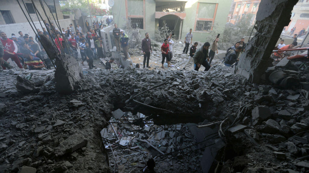 Los palestinos se reúnen alrededor de un edificio afectado por un ataque aéreo israelí, en el sur de la Franja de Gaza, el 5 de mayo de 2019.