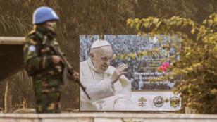 Un soldat de la Minusca monte la garde à l'extérieur du stade Barthélemy Boganda de Bangui le 28 novembre 2015, près d'un panneau annonçant la visite du pape François.