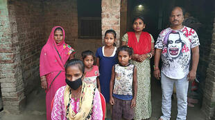 جيوتي كوماري باسوان (أسفل الصورة) مع عائلتها أمام منزلهم في قرية سيروهولي في قضاء داربهانغا في 23 ايار/مايو 2020، بعدما قطت مسافة اكثر من 1200 كيلومترا مع والدها  في انحاء الهند على متن دراجة هوائية.