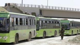 حافلات عند مدخل حرستا في الغوطة الشرقية تنتظر للانطلاق وهي تقل مقاتلين ومدنيين من هذه المنطقة إلى إدلب في 25 آذار/مارس 2018