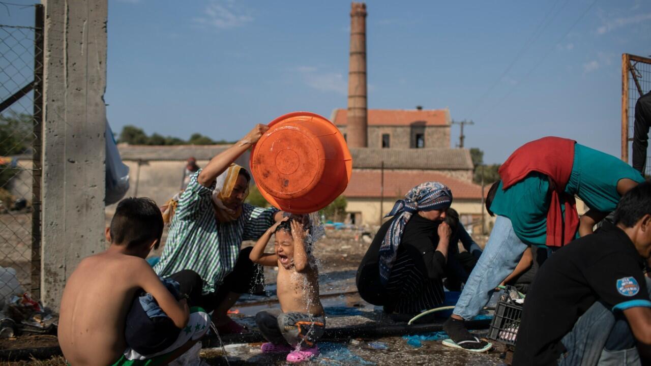 Una mujer lava a una niña mientras los migrantes se reúnen cerca de la ciudad de Mytilene, en la isla nororiental de Lesbos, Grecia, el sábado 12 de septiembre de 2020.