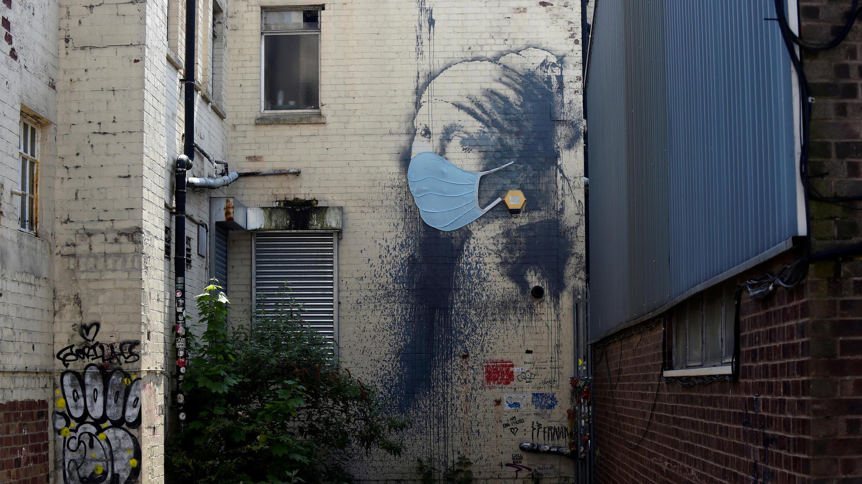 """Una pieza de arte callejero de Banksy titulada """"La chica del tímpano perforado"""", ahora adornada con una máscara facial protectora, se ve en el muelle de Albion, en medio de la propagación del coronavirus en Bristol, Gran Bretaña 23 de abril de 2020"""