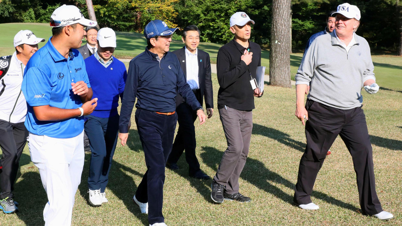 El presidente estadounidense Donald Trump dialoga con el primer ministro de Japón, Shinzo Abe, mientras el golfista profesional japonés Hideki Matsuyama los observa, durante el juego de golf en el Kasumigaseki Country Club en Kawagoe, el 5 de noviembre de 2017.
