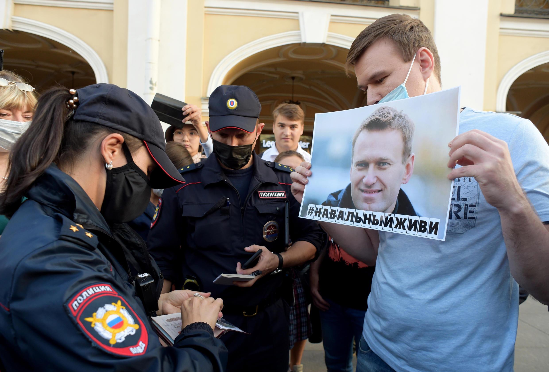 Agentes de policía revisan los documentos de un hombre que sostiene un cartel con una imagen de Alexéi Navalny durante una manifestación para expresar su apoyo al líder de la oposición rusa en el centro de San Petersburgo el 20 de agosto de 2020.