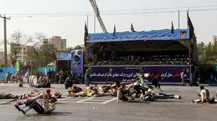 Alireza Mohammadi, ISNA/AFP | This picture taken on September 22, 2018 in the southwestern Iranian city of Ahvaz shows injured soldiers lying on the ground at the scene of an attack on a military parade that was marking the anniversary of the outbreak of its devastating 1980-1988 war with Iraq.