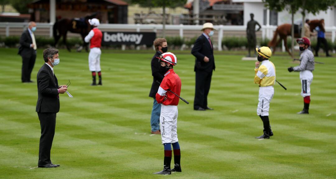 Jinetes hablan con sus entrenadores manteniendo la distancia de seguridad mientras se reanudan las carreras de caballos en Newmarket, Reino Unido, el 4 de junio de 2020.