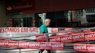 Un Brésilien passe devant une banque fermée pour cause de grève, à São Paulo, le 14juin2019.
