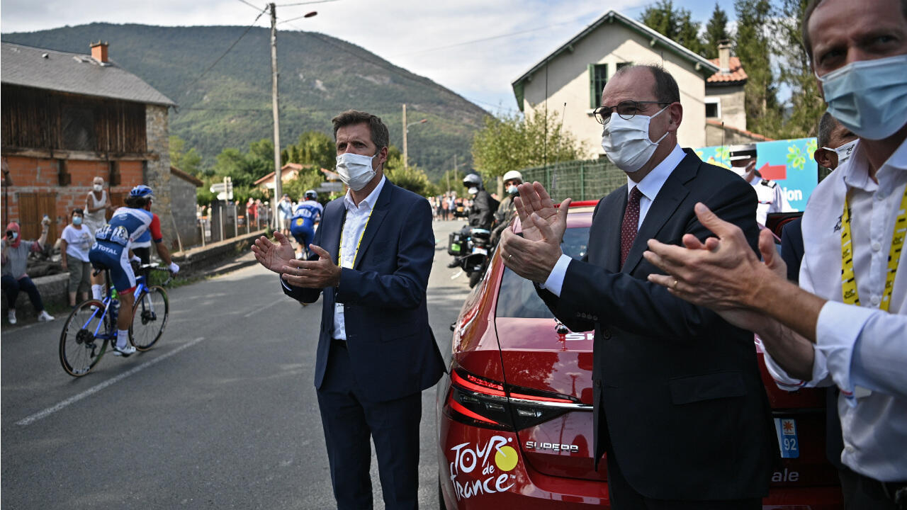 Tour de France Director Christian Prud'homme (right) and French Prime Minister Jean Castex (2nd right) applaud the riders during the 8th stage of the Tour de France cycling race on September 5, 2020.