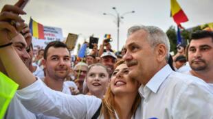 El líder del partido socialdemócrata (PSD), Liviu Dragnea, posa para una selfie con un manifestante junto a la sede del gobierno rumano en Bucarest, Rumania 9 de junio de 2018.
