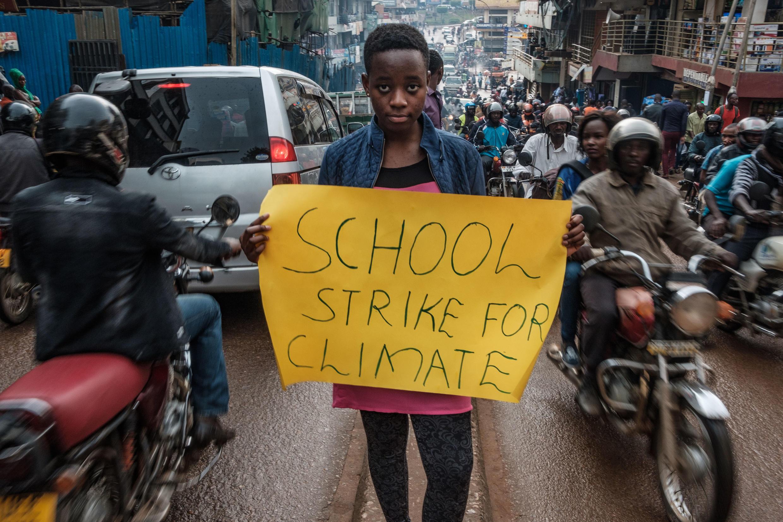 Leah Namugerwa, 15 ans, brandissant une pancarte pour le climat, dans les rues de Kampala, le 4 septembre 2019.