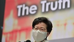 Carrie Lam spoke in front of a backdrop filled with pictures of violent protests alongside the slogan 'The Truth About Hong Kong'