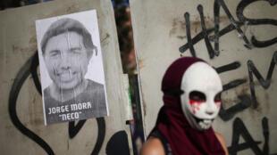 Un protestante con máscara al frente de un poster de Jorge Mora, hincha del equipo de fútbol Colo Colo que murió atropellado por un camión de la policía, en Santiago de Chile, 31 de enero de 2020.