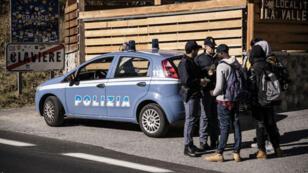 Des policiers italiens contrôlent les papiers de migrants, le 21 octobre 2018, à Clavière, à la frontière entre la France et l'Italie.