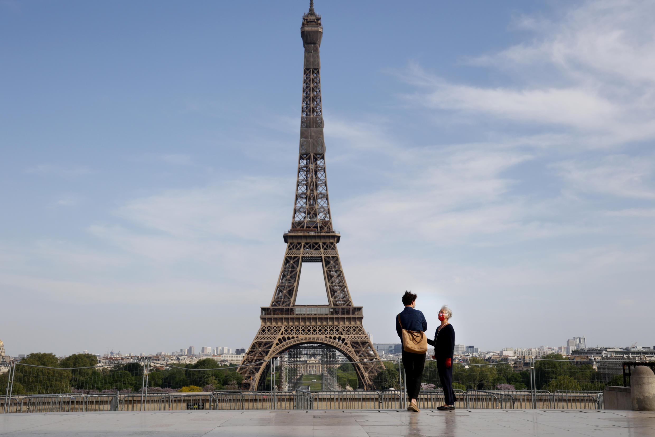 File photo of people wearing a face mask  stand on the empty Trocadero esplanade  near the Eiffel Tower in Paris, on April 20, 2020,