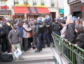 Les travailleurs sans-papiers, isolés par un cordon de CRS, tentent de communiquer avec le Comité de soutien unitaire aux sans-papiers de la rue du Regard.