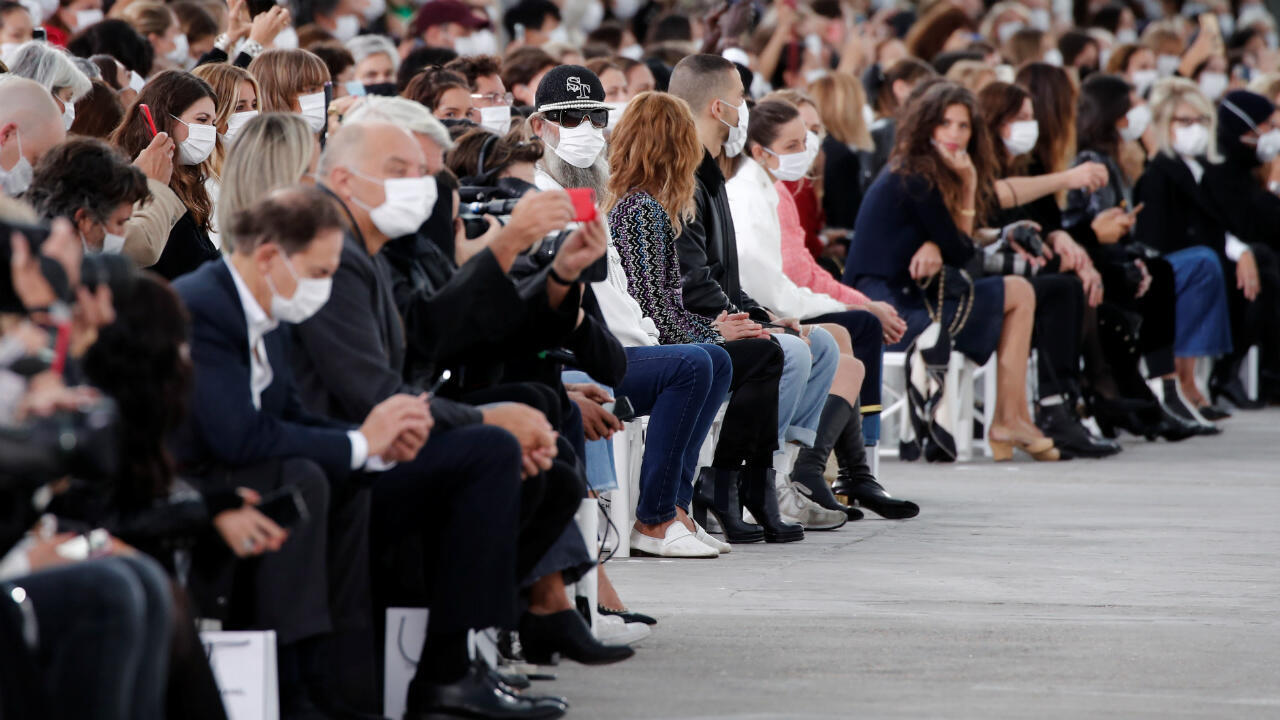 Guests wearing face masks attend the Spring/Summer 2021 ready-to-wear collection show by designer Virginie Viard for fashion house Chanel in Paris on October 6, 2020.