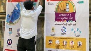 Un employé accroche des affiches à l'entrée d'un centre de vaccination, le 15 janvier 2021 à Bombay, la veille du début de la campagne de vaccination contre le Covid-19 en Inde