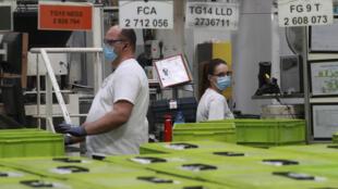 Unos empleados trabajan en una fábrica del proveedor del sector automotriz Valeo en Etaples, el 26 de mayo de 2020, durante una visita del presidente de Francia, Emmanuel Macron