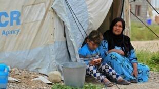 Una mujer y un niño sentados en la entrada de una tienda de campaña en el campamento de Laylan, a 25 km de la ciudad iraquí de Kirkuk, el 9 de mayo de 2019.
