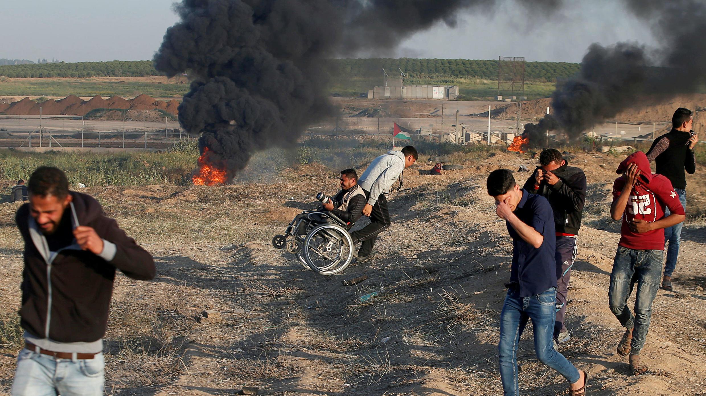 Un fotógrafo palestino en silla de ruedas recibe ayuda, mientras otros huyen a causa del gas lacrimógeno, disparado por tropas de Israel, durante las protestas en la frontera entre Israel y Gaza donde los manifestantes exigen el derecho de los palestinos a regresar a su tierra natal, al este de la ciudad de Gaza, el 1 de abril de 2018.