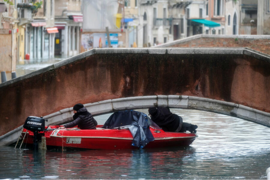 A boat attempts to pass under a bridge amid Venice flooding on November 15, 2019.