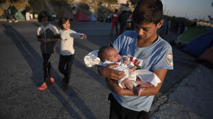 A boy carries his newborn brother after sleeping on a main road at the island of Lesbos