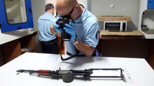 Des gendarmes français examinent une arme utilisée par les attaquants de l'hôtel Radisson Blu le 20 novembre.